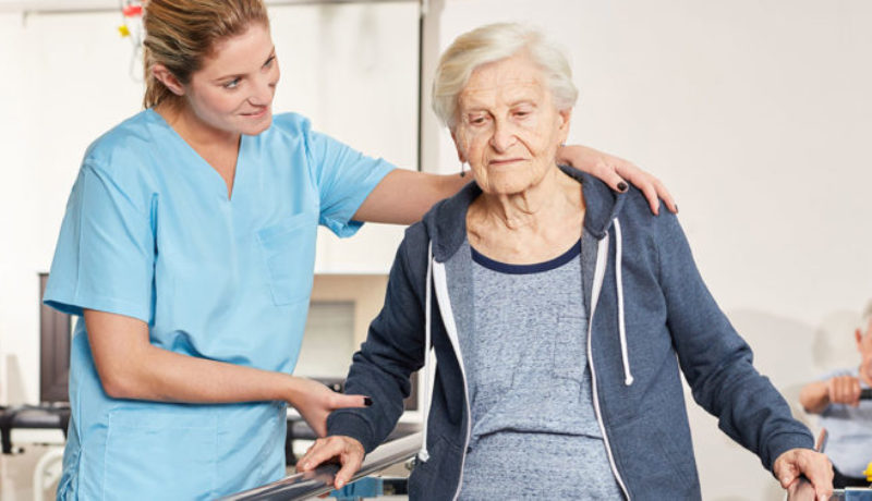 Rehabilitation therapist supports senior woman on treadmill in physiotherapy.